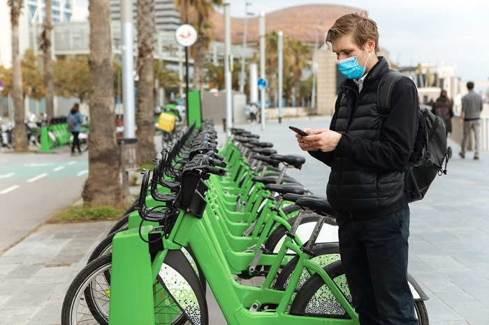 Young,Man,Unlocks,Bicycle,With,His,Mobile,Phone.,Electric,Bicycle